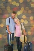 Attractive young couple ready to go on vacation against close up of christmas lights