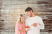Attractive couple holding miniature house model against wooden planks