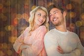 Attractive couple smiling with arms crossed against close up of christmas lights