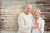 Happy mature couple with model house against wooden planks