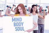 Pretty redhead showing a poster against mind body soul