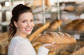 Pretty brunette holding loaf of bread at the bakery
