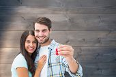 Happy young couple holding new house key against bleached wooden planks background