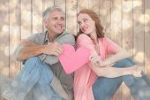 Casual couple holding pink heart against light glowing dots design pattern