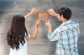 Happy young couple putting up picture frame against bleached wooden planks background