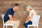 Young couple sitting in chairs arguing against wooden planks background