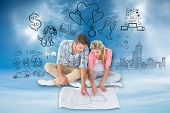 Attractive young couple sitting looking at blueprint against blue sky