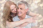 Casual couple hugging and smiling against light glowing dots design pattern