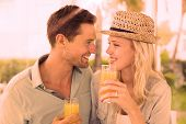 Hip young couple drinking orange juice together on the cafe terrace on sunny day