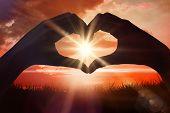Hands making heart shape on the beach against sunrise over grass