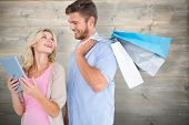Attractive young couple holding shopping bags looking at tablet pc against bleached wooden planks background