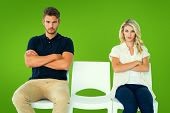 Young couple sitting in chairs not talking during argument against green vignette