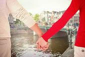Couple holding hands rear view against canal in amsterdam