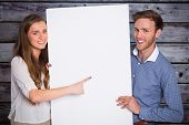 Happy young couple with blank board against grey wooden planks