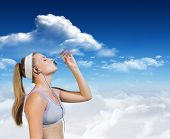 Sporty blonde drinking water against bright blue sky with clouds