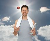Smiling fit young man with apple and water bottle against sky