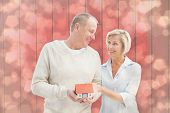 Happy mature couple with model house against light glowing dots design pattern