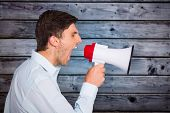 Young man shouting through megaphone against grey wooden planks