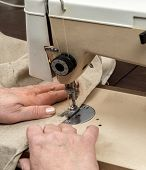 Closeup of senior woman's hands sawing linen border with sewing machine
