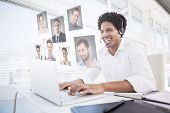Happy businessman working at his desk wearing headset against profile pictures