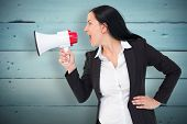 Pretty businesswoman shouting with megaphone against painted blue wooden planks