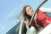 pic of car-window  - Car driver woman happy showing car keys out window - JPG