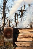 picture of smoker  - Hand built BBQ smoker with wood stacked beside in a rural setting - JPG