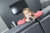 A cute little girl with remote control in front of TV.