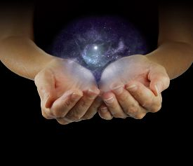 picture of wicca  - Female with cupped hands emerging from black background apparently holding a Galaxy in  her hands - JPG