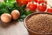 stock photo of ceramic bowl  - Composition with ceramic bowl dry buckwheat eggs tomatoes and parsley in the background - JPG