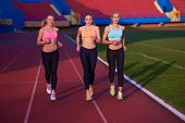 picture of race track  - athlete woman group  running on athletics race track on soccer stadium and representing competition and leadership concept in sport - JPG