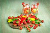 picture of strawberry  - Strawberry loose strawberry ice cream on a wooden kitchen Boards on turquoise background drink a glass of strawberry cucumber ice - JPG