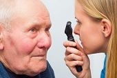 image of cataract  - Optician consulting elderly patient with cataracts and other eye problems - JPG