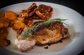 stock photo of roasted pork  - Pork steak with roasted carrots and dried tomatoes on white plate - JPG