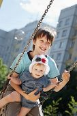 picture of swing  - Boy swinging with her younger sister on a swing - JPG