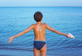 picture of sunburn  - handsome preteen boy with anti sunburn cream sun drawing on his back on the sea sand beach background - JPG