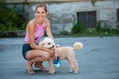 image of poodle  - Beautiful young woman on a walk with cute poodle dog - JPG