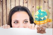 stock photo of peeking  - Pretty brunette peeking at chocolate against wooden planks - JPG
