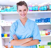 pic of scrubs  - Smiling nurse in blue scrubs posing with arms crossed against close up of shelves of drugs Smiling nurse in blue scrubs posing with arms crossed on white background - JPG