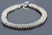 image of precious stones  - Beautiful golden bracelet with precious stones on grey background - JPG