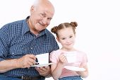 image of granddaughter  - Portrait of a grandfather wearing blue checkered and his small pretty granddaughter playing drinking tea from white cups smiling happily - JPG