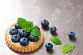 foto of curd  - Shortbread home made tartlet filled with lime curd and blueberries on old vintage metal background - JPG