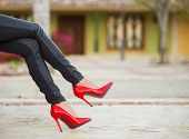 stock photo of black heel  - Woman in black leather pants and red high heel shoes sitting on bench - JPG
