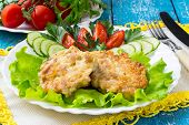 picture of pork cutlet  - Delicious homemade pork cutlets with vegetables on a plate napkin with yellow trim and cutlery on a blue wooden background - JPG