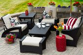 stock photo of spring break  - Overview of Upscale Patio Set Dark Wicker Luxury Furniture with Comfortable Cushions on Outdoor Stone Patio of Affluent Home - JPG