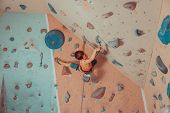 image of harness  - Boy in harness and safety equipment climbing on practical wall indoor - JPG