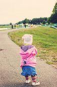 foto of girl walking away  - Toned portrait of Cute Little girl walking away on the road ahead - JPG