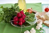 image of radish  - Horizontal photo of Fresh just harvested bunch of radishes on green towel together with spinach leaves mushrooms onions and garlic - JPG