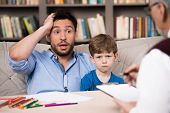 picture of psychologist  - Sad little boy and his uptight father talking with psychologist - JPG