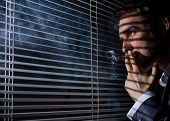 stock photo of blind man  - business man smokes at the window blinds - JPG